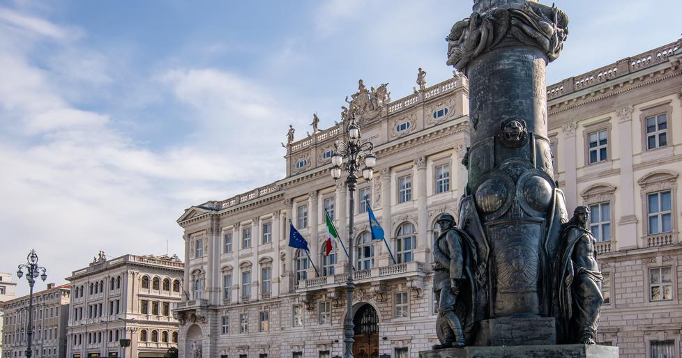 La base dell'imponente portabandiera con sullo sfondo Palazzo Lloyd Triestino, sede della Regione autonoma Friuli Venezia